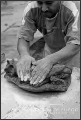 And an artisan spreads the Tierra clay with his hands.